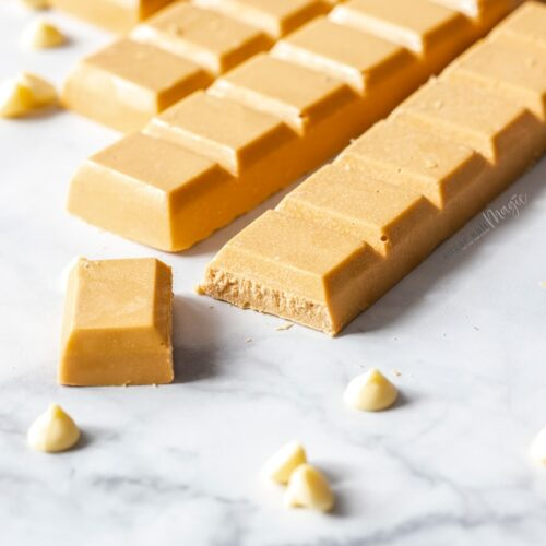 Bars of caramelised white chocolate on a marble surface, surrounded by white chocolate chips