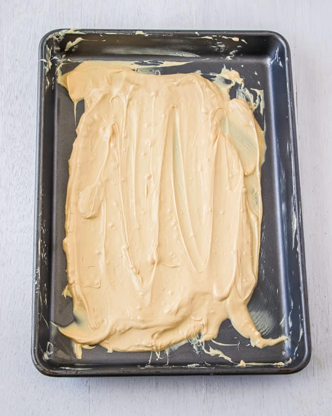 A baking tin covered in melted white chocolate that is being caramelised
