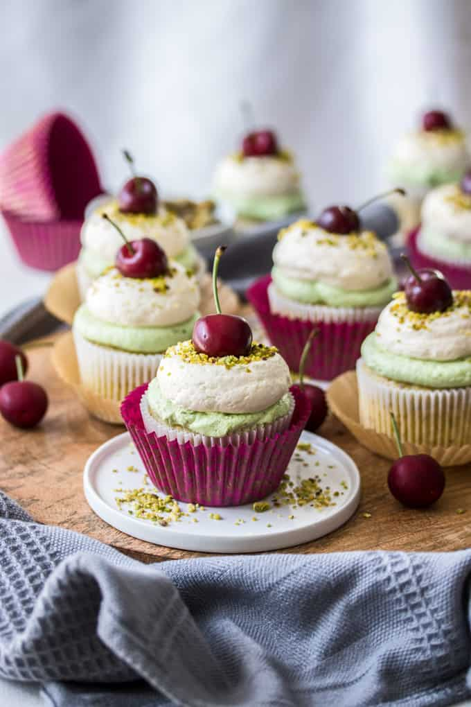 A Cherry Pistachio Cupcake on a small white plate, more cupcakes in the background.