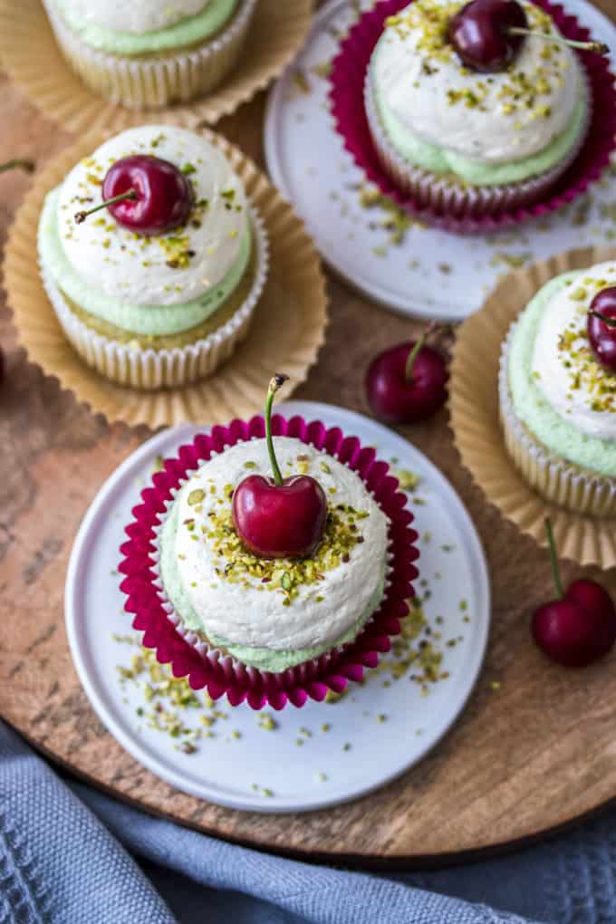 Overhead view of cupcakes with pistachio crumbs and a fresh cherry on top.
