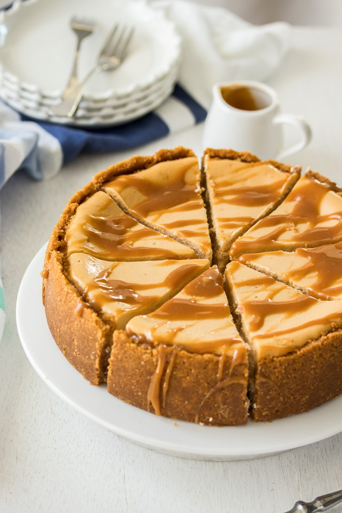 A cheesecake drizzled with caramel sauce on a white cake plate.