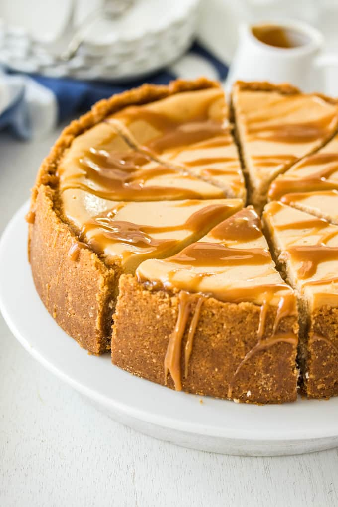 Closeup of a cheesecake drizzled with caramel sauce on a white cake plate.