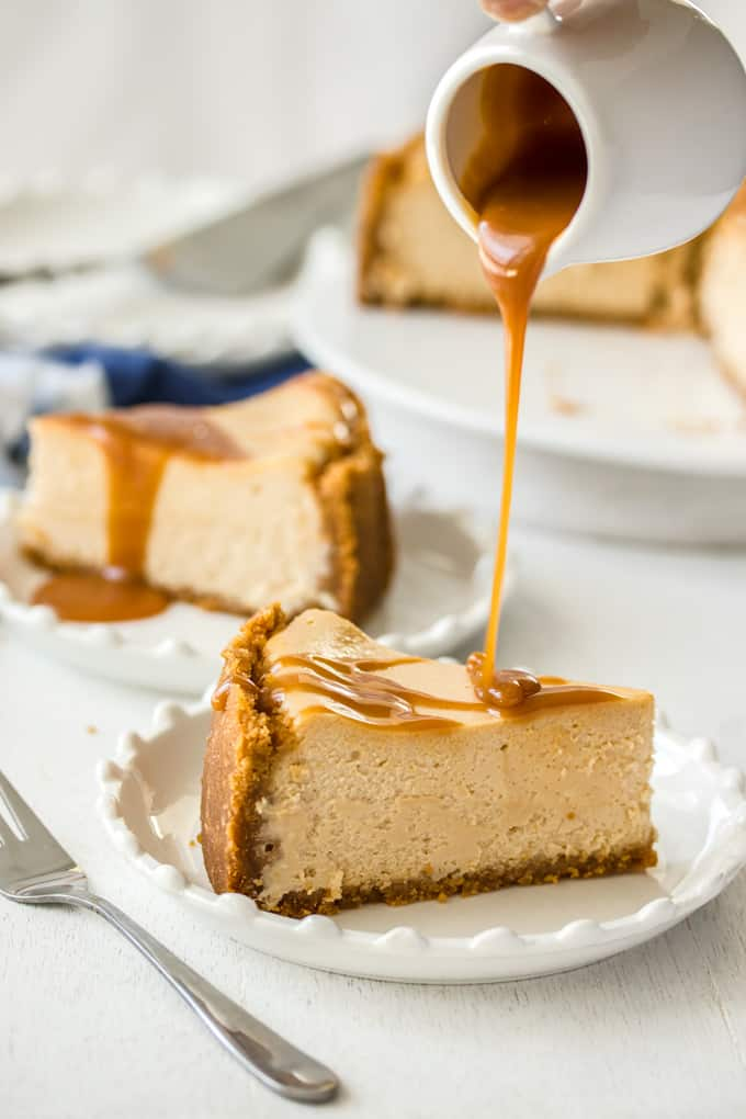 Caramel sauce being drizzled over a cheesecake.