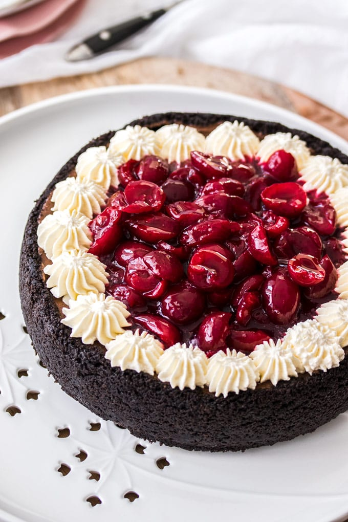 A chocolate cheesecake topped with cream and cherry sauce on a white platter and wooden board