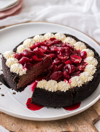 A chocolate cheesecake topped with cherries and whipped cream sittng on a white platter and wooden board