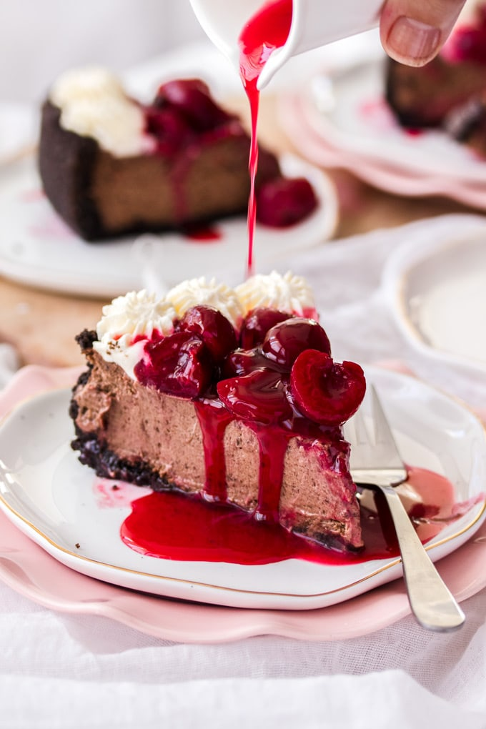 A black forest cheesecake being drizzled with a cherry sauce