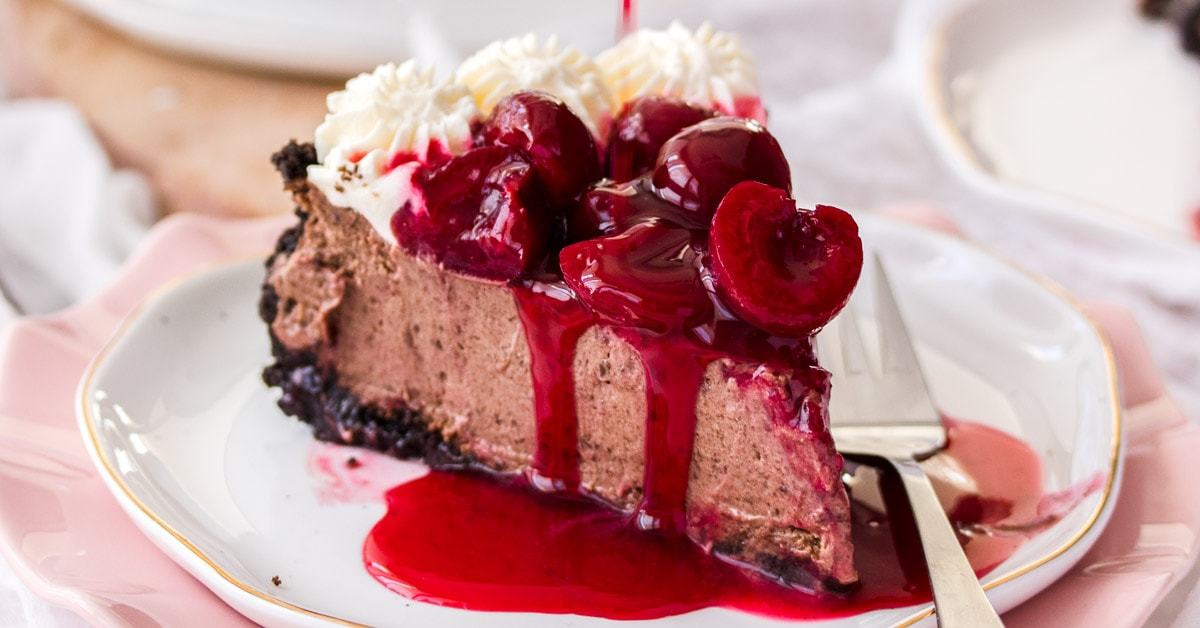 A slice of chocolate cheesecake topped with cream and cherry sauce on a white plate