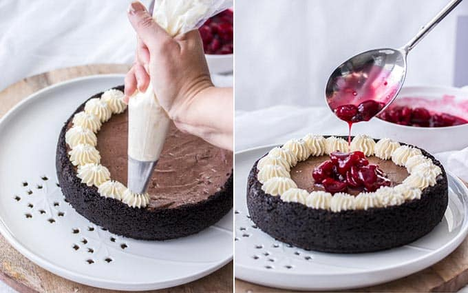Piping cream and pouring cherry sauce onto a chocolate cheesecake that sits on a white platter
