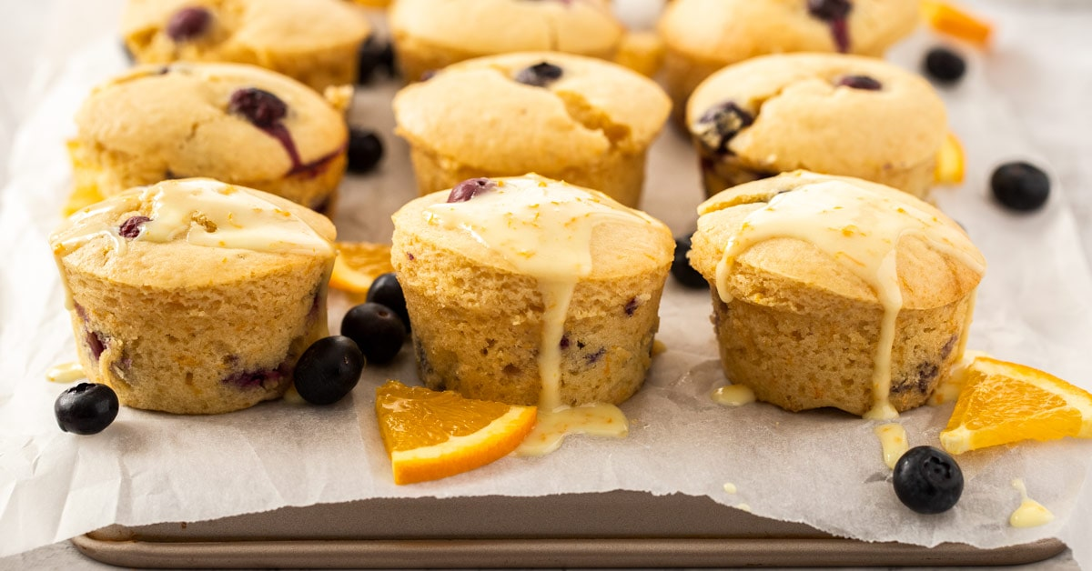 Muffins sitting on a sheet of baking paper on a baking tray. surrounded by blueberries and slices of orange