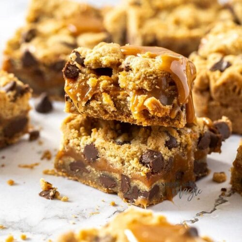 2 stacked cookie bars filled with chocolate chips and caramel on a white white marble surface
