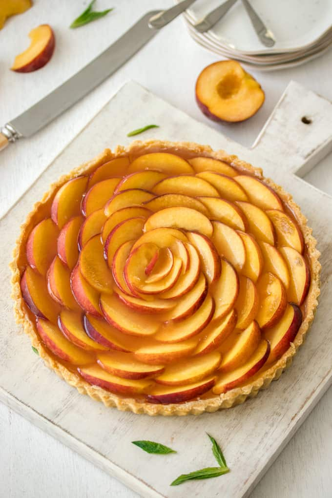 A whole tart decorated with fresh peach slices arranged in concentric circles
