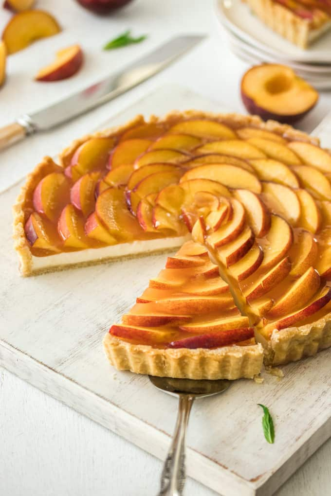 A Panna Cotta Fresh Peach Tart on a white board, a slice is missing, another slice on a cake server