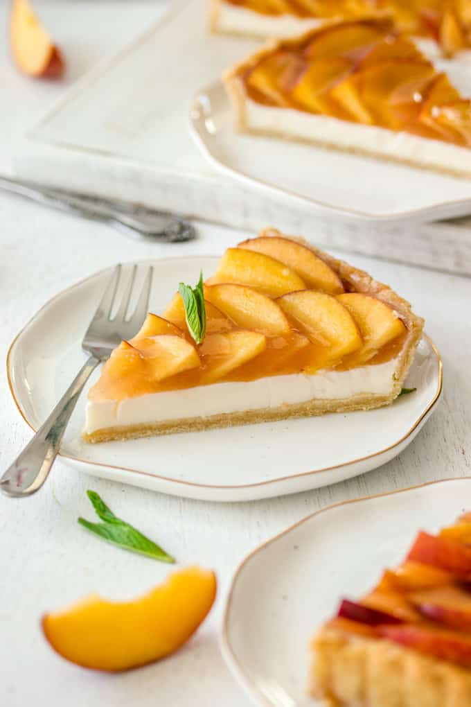 A slice of Panna Cotta Fresh Peach Tart on a white plate with gold rim, a fork resting on the side