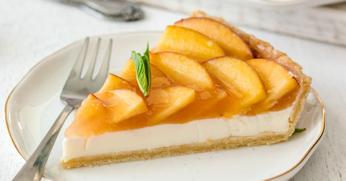 Closeup of a slice of Panna Cotta Fresh Peach Tart showing the distinct layers