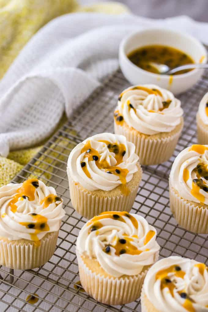 Cupcakes on a wire rack, drizzled with passionfruit.