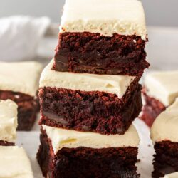 A stack of 3 red velvet brownies with more around it