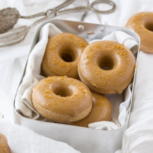 Cake donuts in a tin with dessert tongs next to them
