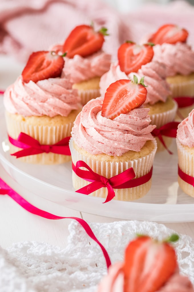 A plate of cupcakes with strawberry buttercream with strawberries on top.