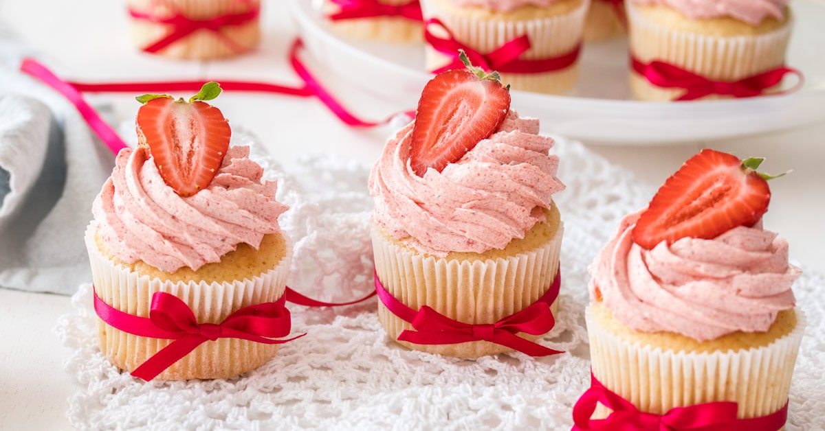 3 vanilla cupcakes with pink buttercream and strawberries on top in a row