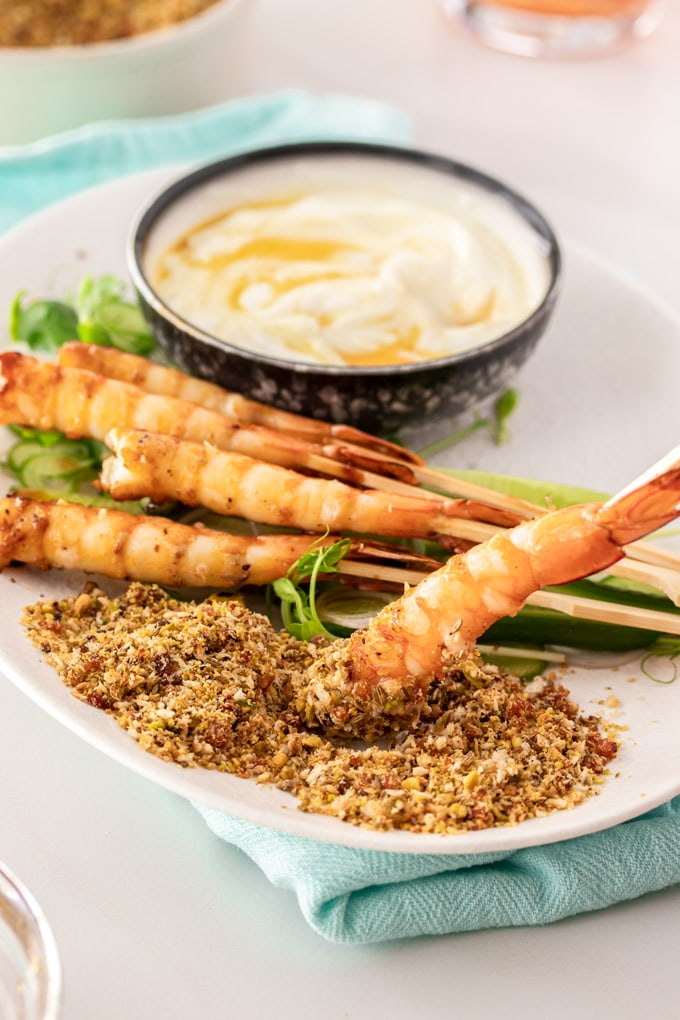 A plate of prawns with one being dipped into dukkah.