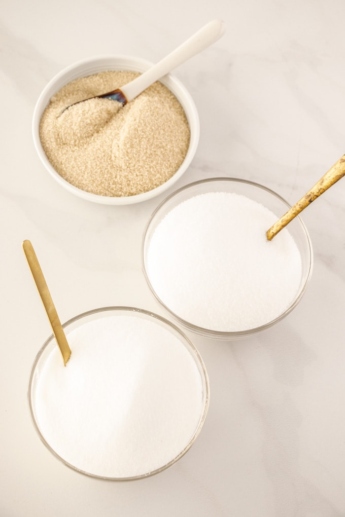Three types of granulated sugar in bowls with spoons