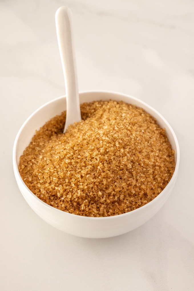 A bowl of demerara sugar with a spoon sticking out