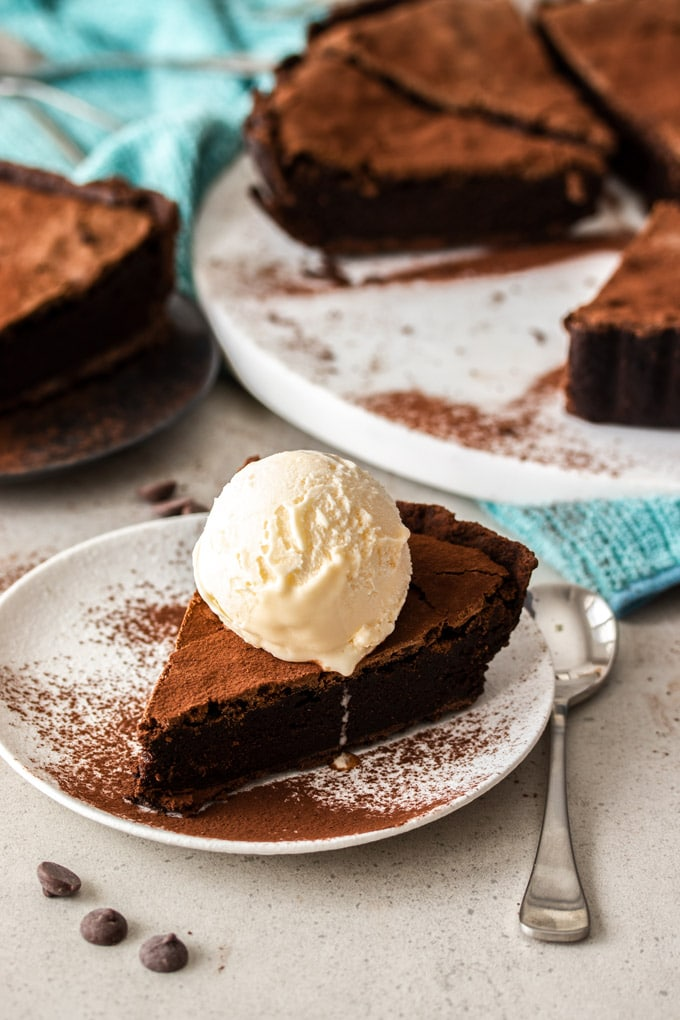 A slice of brownie pie sitting on a white plate with the remaining pie in the background