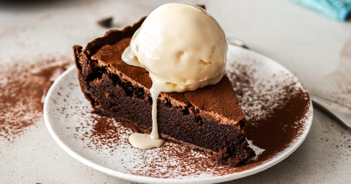 A wide shot of a slice of brownie pie with ice cream on top