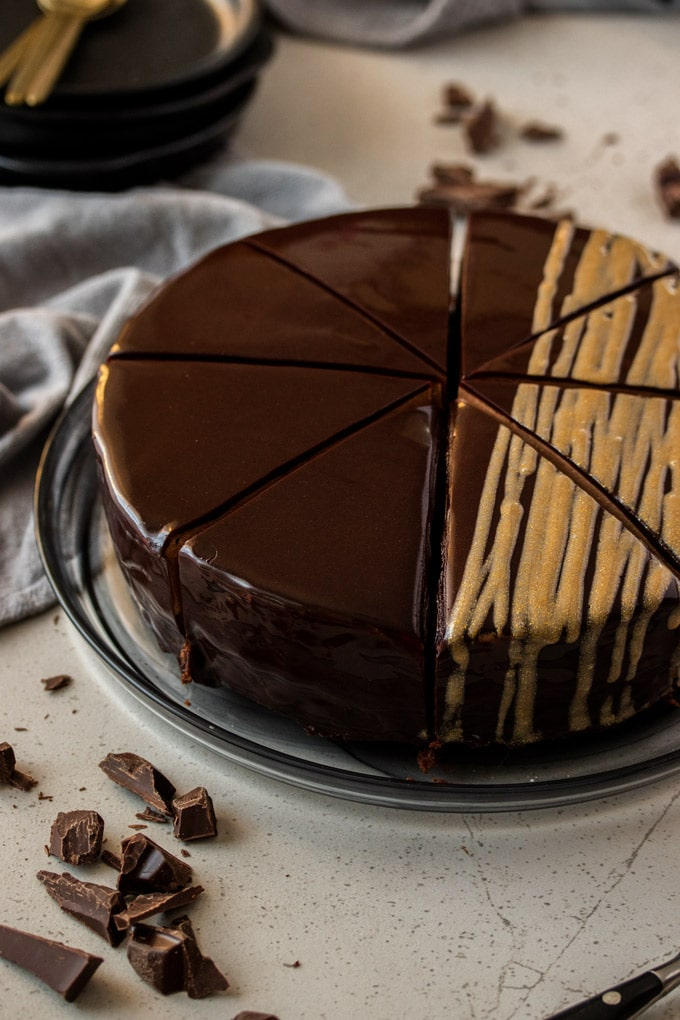 A whole chocolate cake cut into slices sitting on a black glass plate
