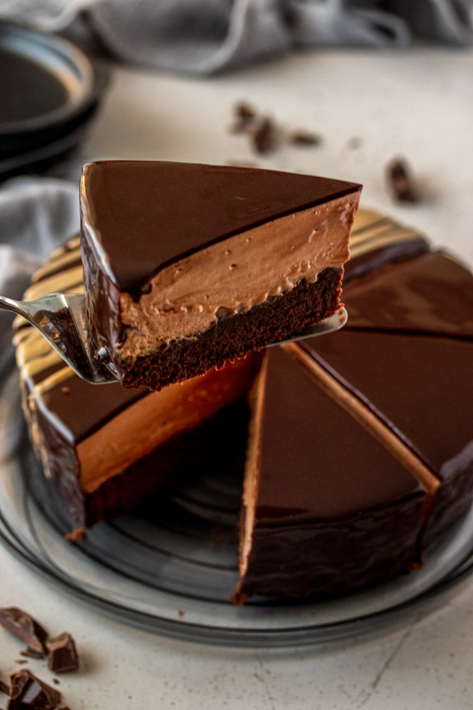 A slice of chocolate mousse mud cake lifted towards the camera. Whole cake in the background.