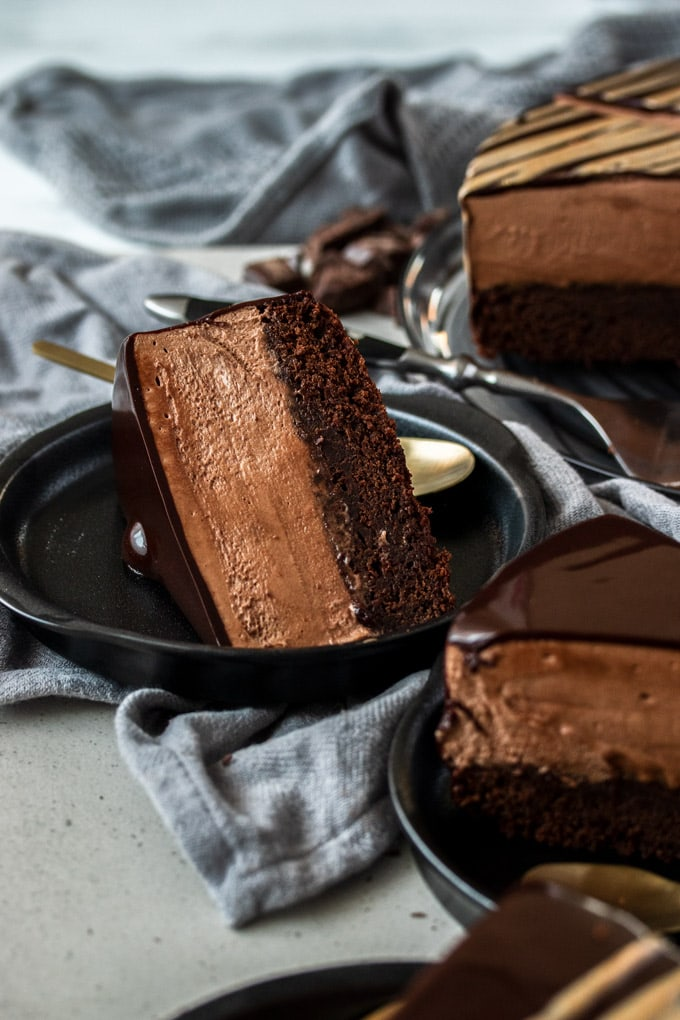 A slice of chocolate mousse mud cake laying on its side on a black plate
