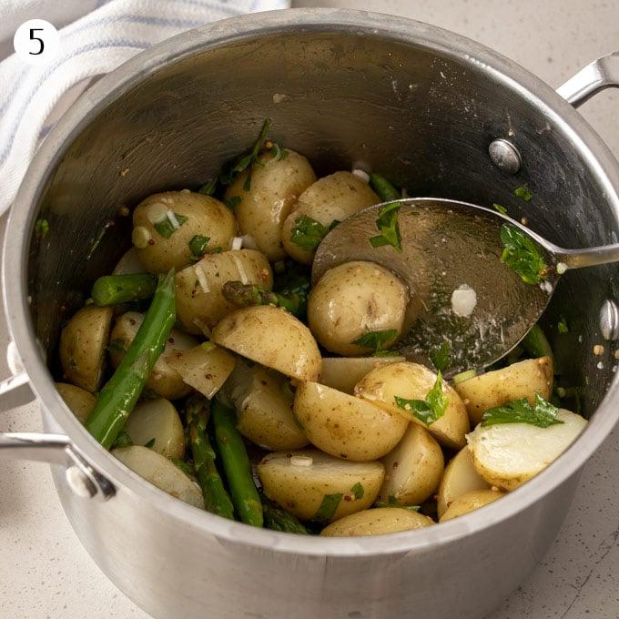 Warm potato asaparagus salad in a saucepan, mixing the vinaigrette through.