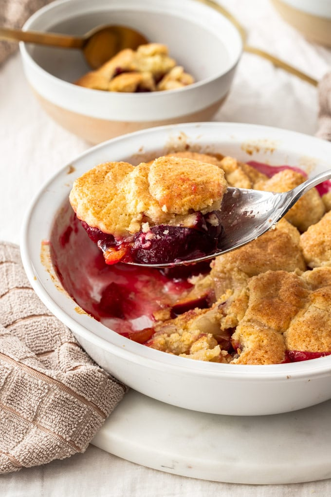 A spoon filled with cobbler dessert, scooping from a white pie dish.