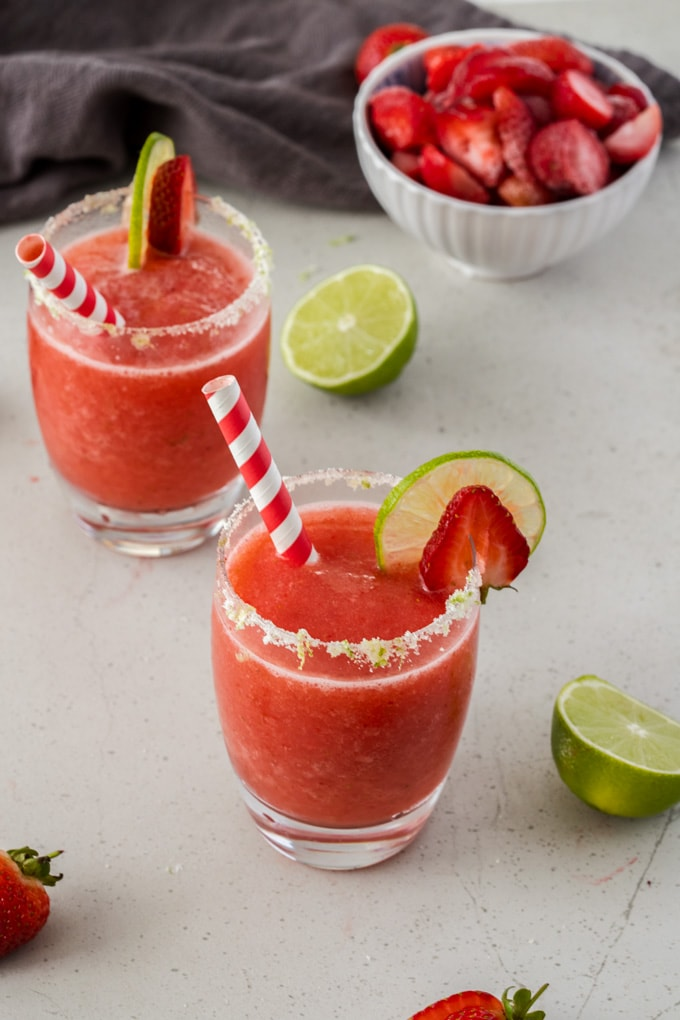 Two glasses filled with frozen strawberry daiquiri with a couple of lime wedges