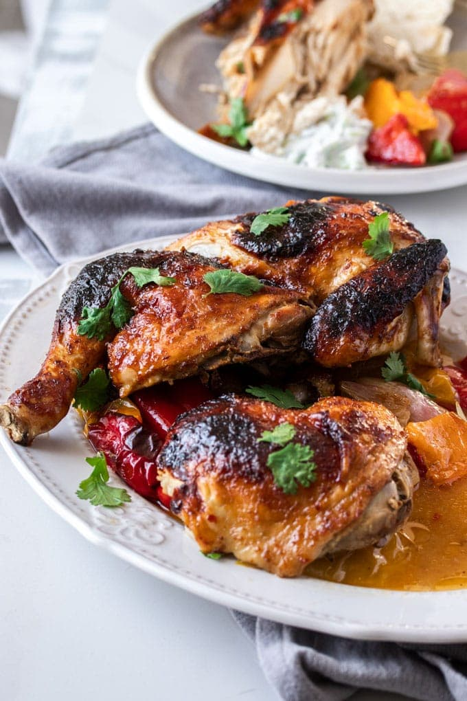 Pieces of roasted harissa chicken on a white platter with an orange sauce on the side