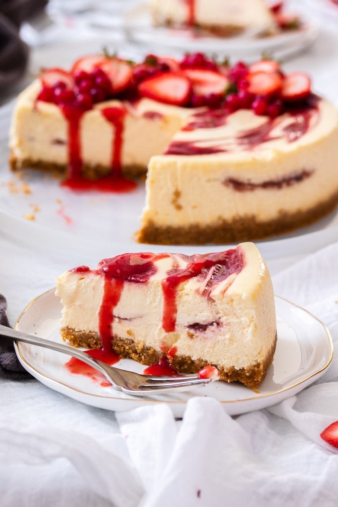 A closeup slice of strawberry swirl cheesecake with the rest of the cheesecake in the background