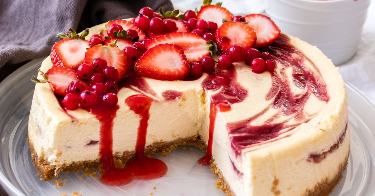 Close up of three quarters of a strawberry swrirl cheesecake