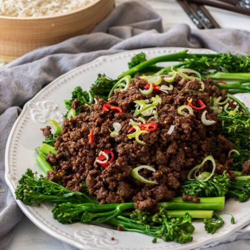A white plate filled with Chilli Beef Mince and broccolini