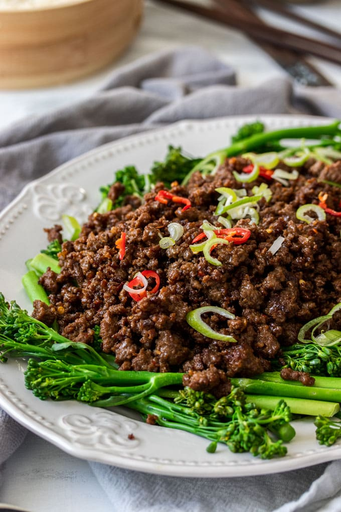 A white platter filled with Asian Chilli Beef Mince and broccolini.