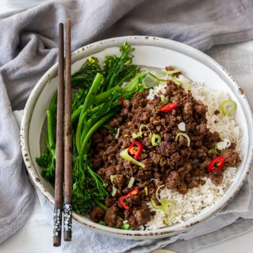 A bowl of rice topped with chilli beef mince and chopsticks