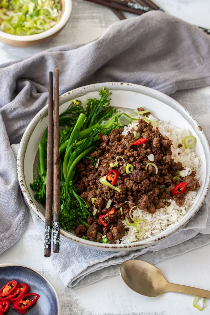 A bowl of rice topped with chilli beef mince, broccolini, and chopsticks resting on the rim.