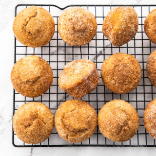 A batch of cinnamon sugar muffins on a black cooling rack on a marble surface