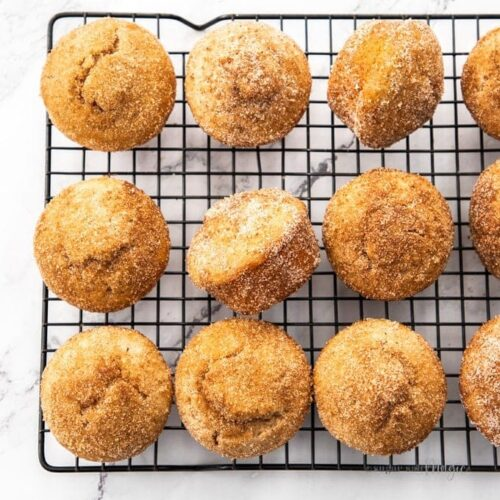 A batch of cinnamon sugar muffins on a black cooling rack on a marble surface.
