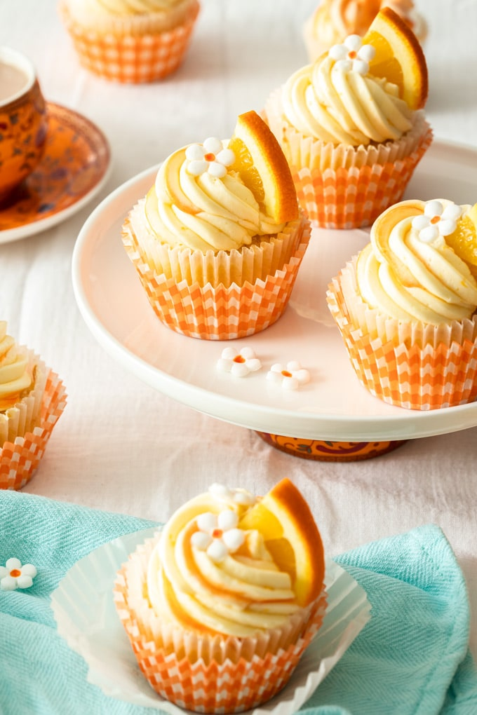 Three orange cupcakes with white buttercream on a white plate