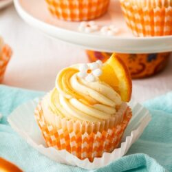 A closeup of an orange cupcake with white frosting.