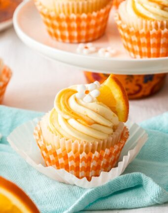 A closeup of an orange cupcake with white frosting