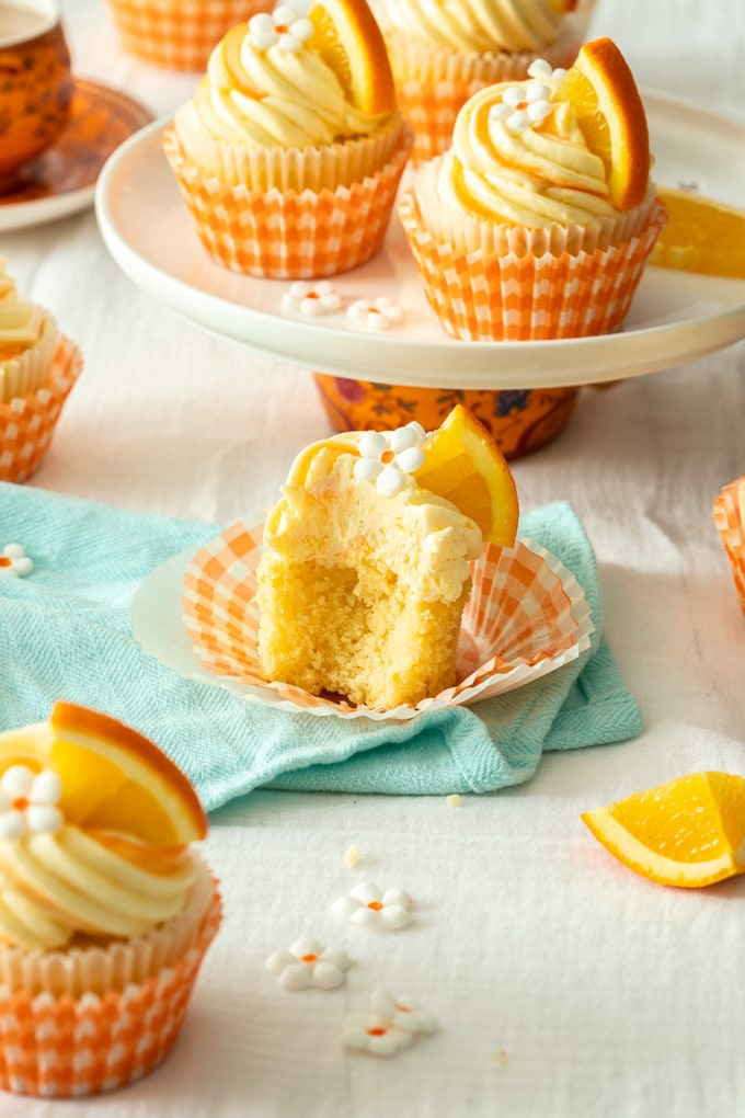 An orange cupcake cut open to reveal the fluffy texture sitting on an aqua teatowel.
