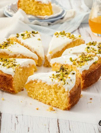 Closeup of a slice of Greek Orange Semolina Cake with more slices surrounding it
