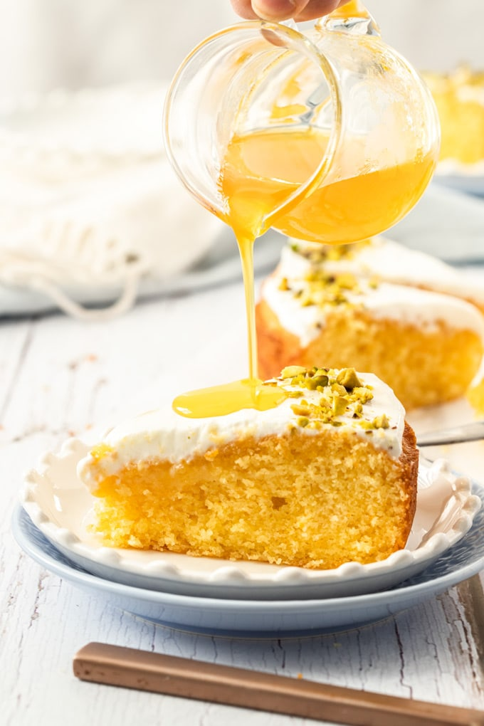 Pouring orange syrup over a slice of cake on a white plate