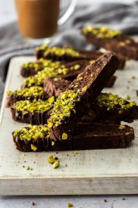 A number of pieces of chocolate biscottion sprinkled with pistachios, piled up on a white board